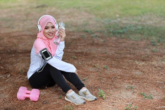 Питьевая вода женщины красивого спортсмена фитнеса азиатская мусульманская после работать. молодая милая девушка сидя в sportswear с гантелью, наушниками принимая остатки после разминки напольной. здоровый, спортивный концепт