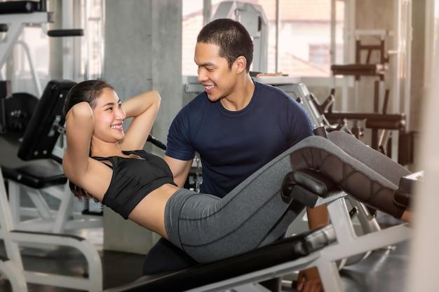 Молодая азиатская женщина в тренировке sportswear сидит вверх с мужским тренером на спортзале фитнеса.
