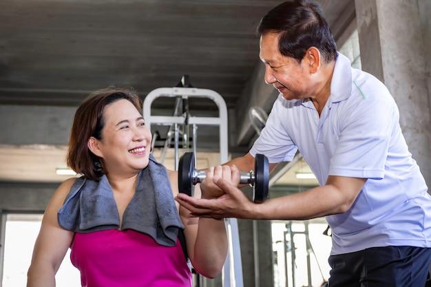 Азиатские старшие пары усмехаясь в sportswear работая на спортзале.