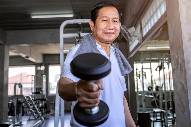 Азиатский старший человек в тренировке sportswear с гантелью на спортзале.
