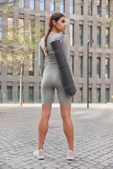Sportiva in abbigliamento sportivo e scarpe da ginnastica posa di nuovo alla macchina fotografica porta tappetino fitness ha allenamento all'aperto pratica yoga passeggiate nel centro durante il giorno va allo stadio della città