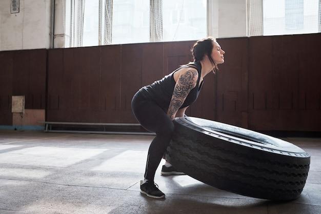 Спортсменка наращивает мускулы. молодая темноволосая женщина с татуированными руками переворачивает тяжелую шину во время перекрестной тренировки в тренажерном зале