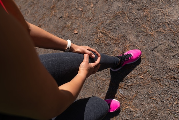 The sportswoman clasped her knee with her hands felling pain after jogging.