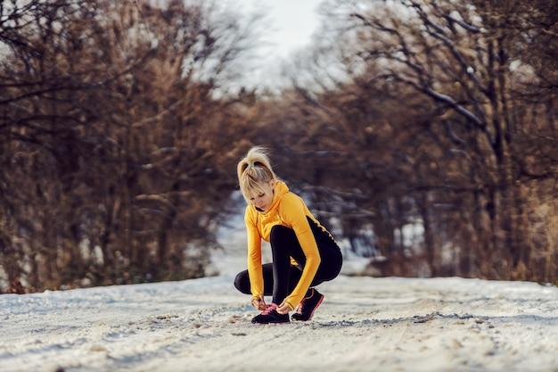 스포츠우먼은 겨울에 자연의 눈 덮인 길에 웅크리고 신발끈을 묶습니다. 스포츠웨어, 겨울 피트니스, 건강한 생활