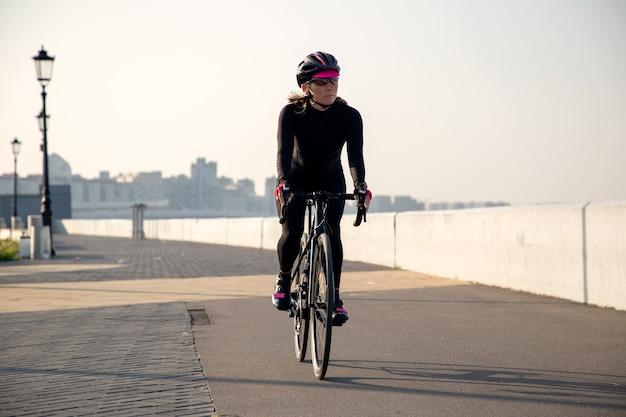 Спортсменка-велосипедистка едет по набережной на рассвете