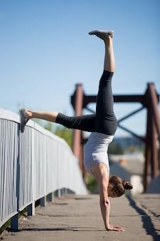 Спортсменка делает баланс упражнения на открытом воздухе