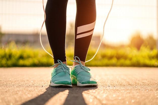 Спортсменка делает кардио упражнения со скакалкой на открытом воздухе