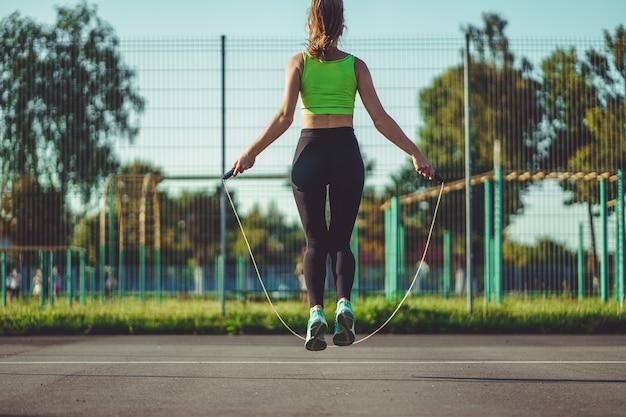Спортсменка делает кардио упражнения с прыжками со скакалкой на открытом воздухе