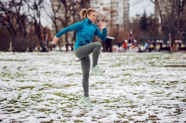 公園で雪の降る天気でフィットネス運動をしているスポーツウーマン。冬のフィットネス、健康的な生活、ウォームアップエクササイズ