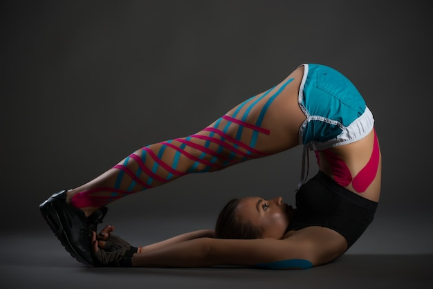 Sportswoman doing flexibility exercises with stickers on her legs