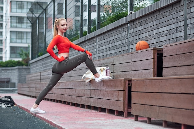 Sportswoman doing leg stretching exercise with medicine ball. fit woman exercising with ball in gym workout.