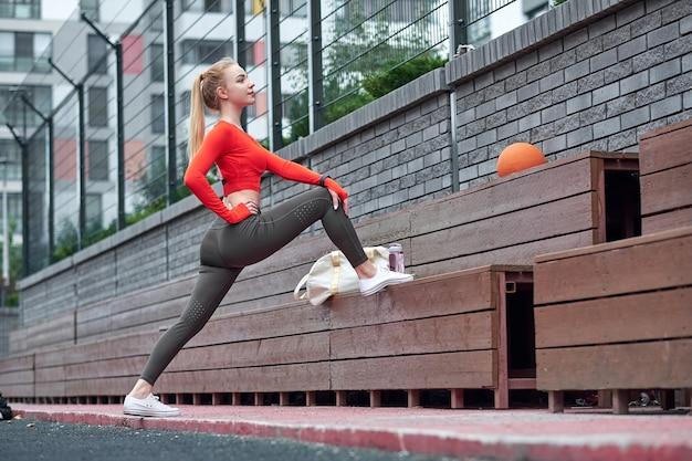 薬のボールで脚のストレッチ運動をしているスポーツ選手。ジムのトレーニングでボールを使って運動している女性にフィットします。