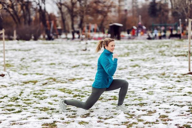 雪の降る天気で公園で突進をしているスポーツ選手。冬のフィットネス、寒さ、公園、雪