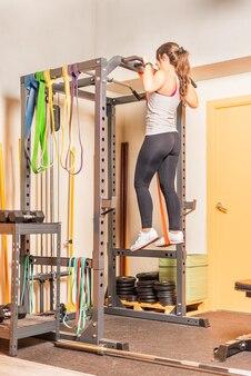 ジムでバーで懸垂をしているスポーツ選手。ジムでの機器を使った運動の概念。