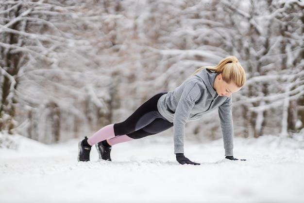 Спортсменка делает отжимания на заснеженной дорожке на природе зимой. зимний фитнес, снежная погода, здоровый образ жизни