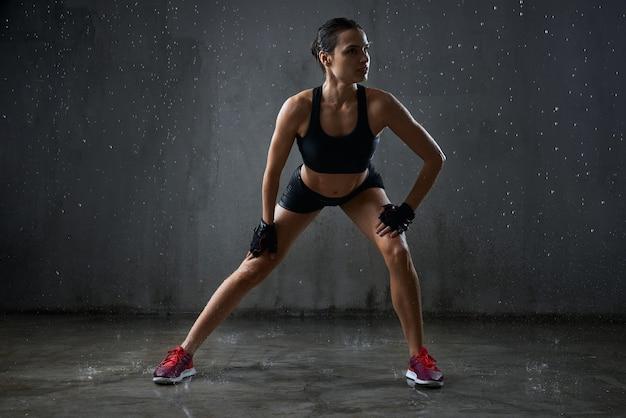 雨の下でサイドランジをしているスポーツ選手