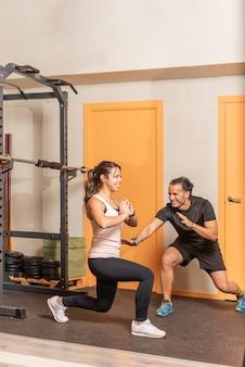 체육관에서 가중 운동 없이 스쿼트를 하는 스포츠우먼. 체육관의 개념입니다.