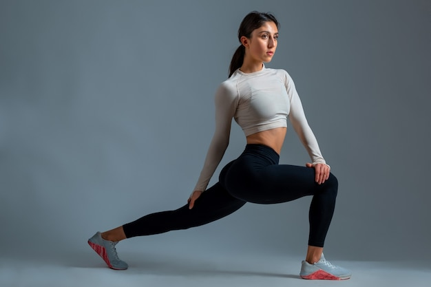 Sportswoman doing stretching lunges with twisting of body on grey wall