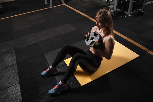 スポーツクラブで加重腹筋運動をしているスポーツウーマン