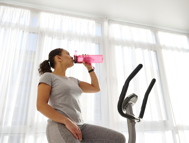 A sportswoman drinking water after cardio training on a stationary bike to stay hydrated