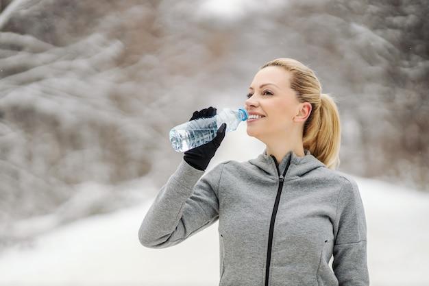 Sportswoman는 물을 마시고 눈 덮인 겨울 날에 자연에 서있는 동안 휴식을 취합니다.