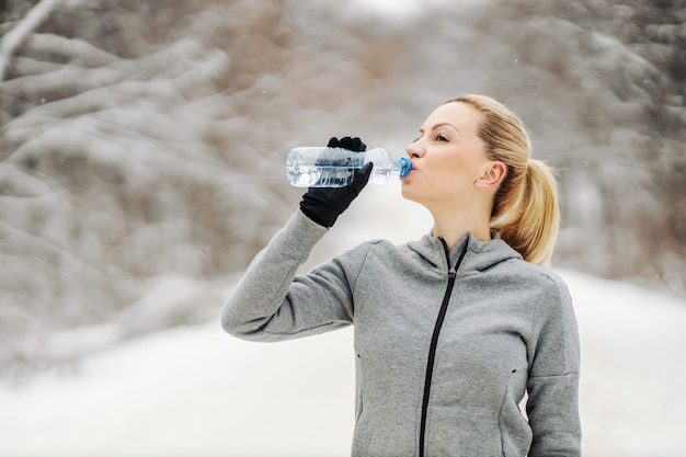 Sportswoman drinking water and taking a break from exercising while standing in woods at snowy winter day. healthy life, winter fitness, refreshment