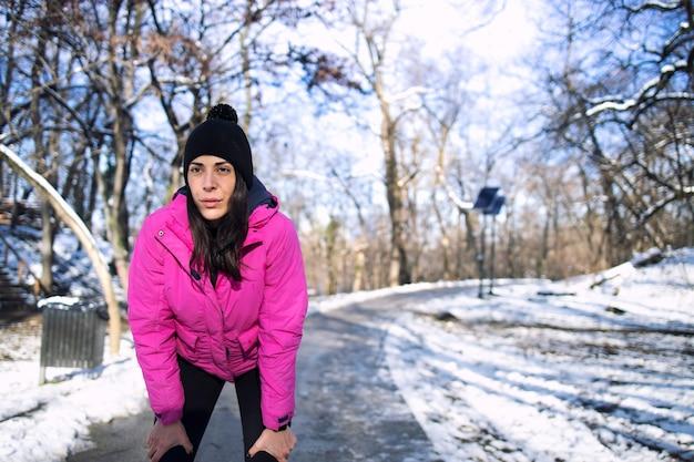 눈이 내리는 동안 겨울 동안 공원에서 운동하는 sportswoman.