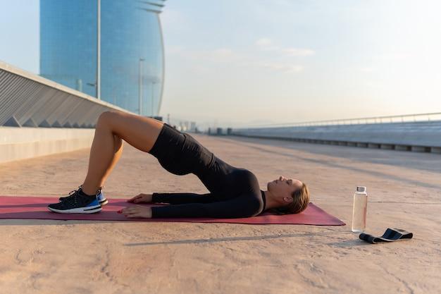 Спортсменка, тренирующаяся на коврике на улице