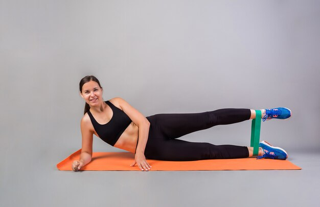 Sportswoman exercising with gymnastic elastic band on the mat