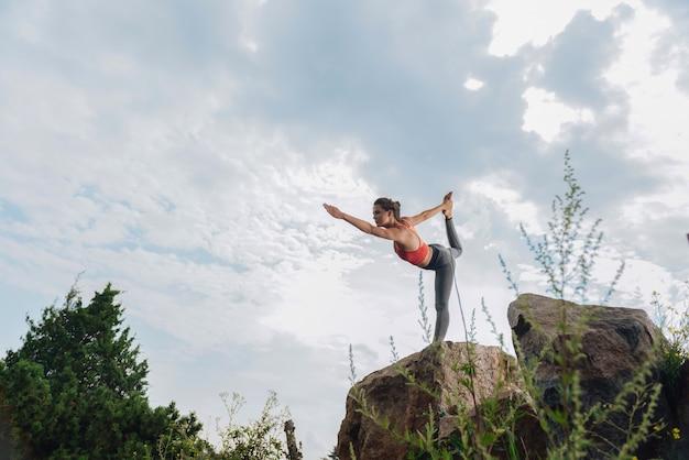 Спортсменка чувствует себя просто потрясающе, растягивая ноги и руки стоя на одной ноге