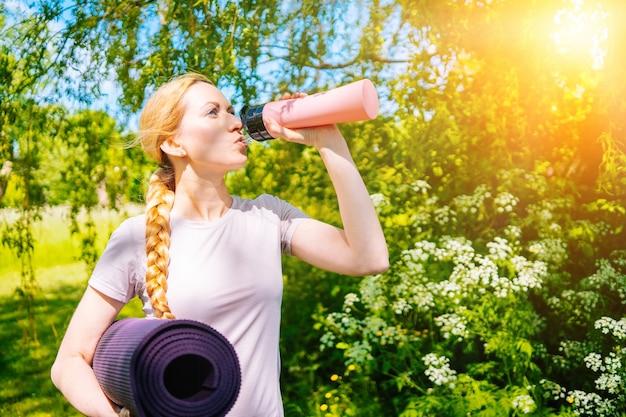 Спортсменка идет на практику йоги с ковриком, готовым к занятиям в тренажерном зале. спортивная девушка держит коврик для йоги и бутылку с водой перед фитнес-тренировкой.
