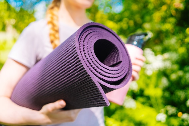 Sportswoman going to yoga practice with mat being ready for exercising in gym sporty girl holding yo...