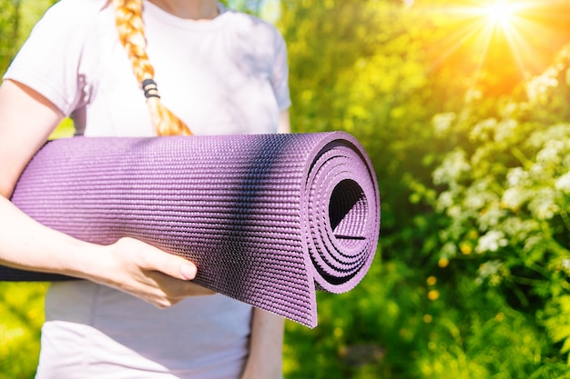 Sportswoman going to yoga practice with mat being ready for exercising in gym sporty girl holding yoga mat and water bottle before fitness training concept of sports active lifestyle and health