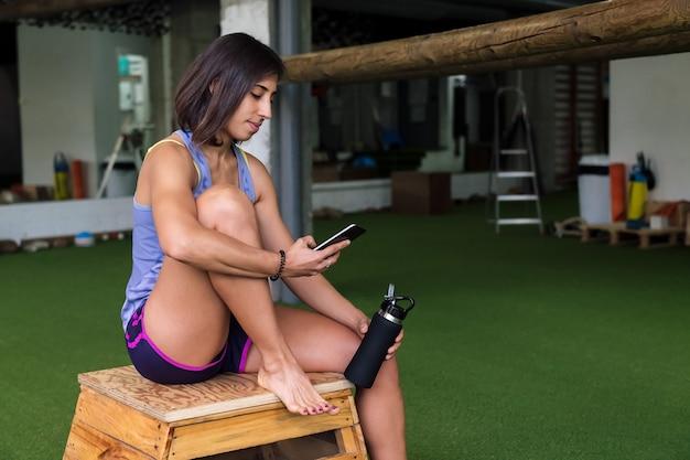 Sportswoman는 병을 들고 체육관에서 전화 상담