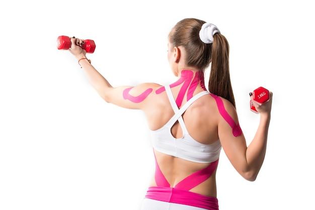 Спортсменка держит гантели с наклейками на плечах и шее