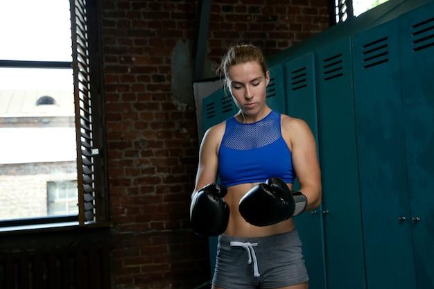 ボクシンググローブを試着するロッカールームのスポーツ選手
