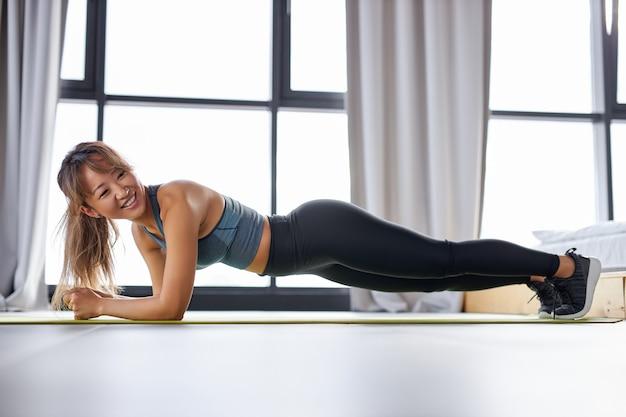 板の位置にいるスポーツウーマン、自宅でのトレーニング、スポーツをお楽しみください。
