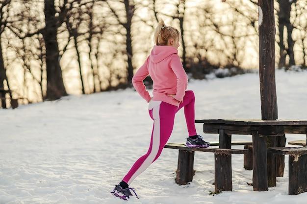눈 덮인 겨울 날 자연에서 벤치에 돌진 하 고 모양에 스포츠 우먼. 건강한 습관, 겨울 피트니스, 야외 피트니스