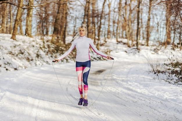 Спортсменка в форме прыгает через скакалку на заснеженной тропе в лесу зимой. зимний фитнес, кардио упражнения