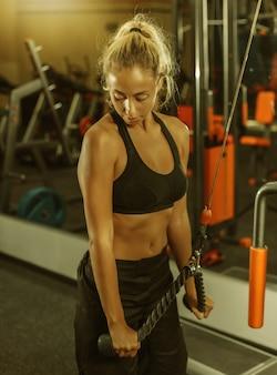 Спортсменка в спортивной одежде тренирует трицепс на тренажере в тренажерном зале