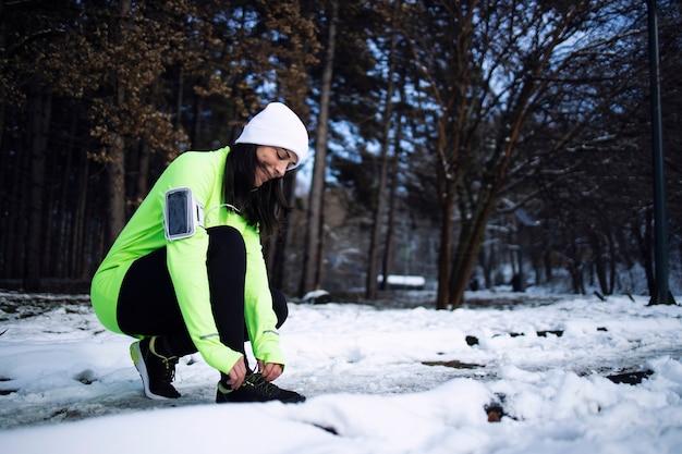 겨울에 공원에서 신발 끈을 묶는 스포티 한 옷에 sportswoman.