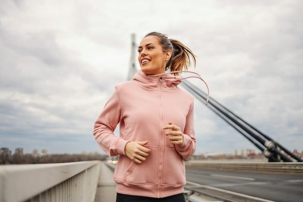 曇りの天気で橋の上でジョギングするトラックスーツのスポーツ選手。健康的なライフスタイルのコンセプト。