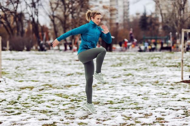 公園でショーでウォームアップ運動をしている暖かい服装のスポーツウーマン。雪の降る天気、冬のフィットネス、肌寒い天気、公園