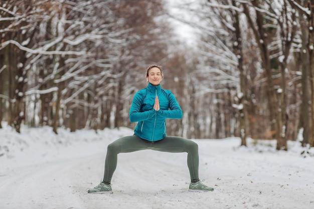 雪に覆われた森でヨガの練習をしている暖かい服装のスポーツウーマン。屋外でのフィットネス、雪、寒さ、自然フィットネス