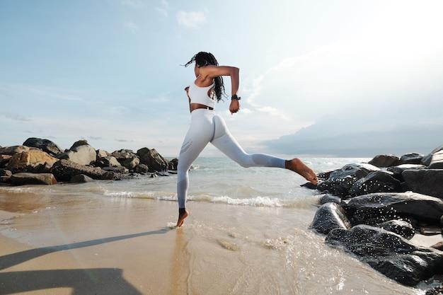 砂浜で走っている白いアクティブウェアのスポーツウーマン