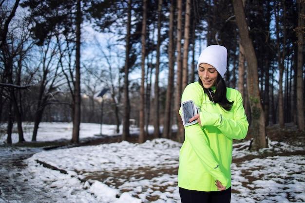 겨울 옷에 운동가는 눈이 내리는 동안 공원에서 훈련하기 전에 노래를 선택합니다.