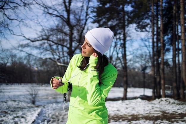 겨울 옷을 입고 운동가는 공원에서 훈련하기 전에 이어폰을 끼고 있습니다.