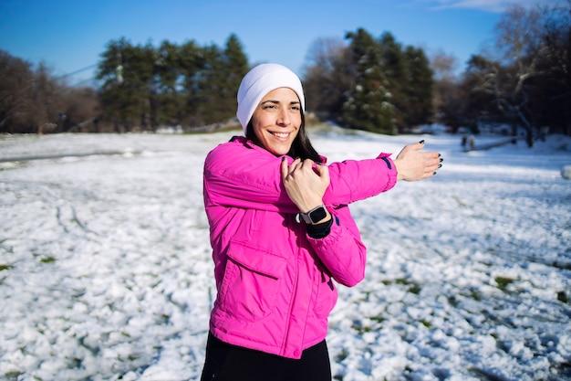 冬のスポーツウーマンは、雪のトレーニングの前に体を伸ばして体を温めます。