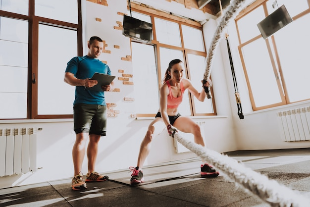 Sportswoman is exercises in gym with trainer