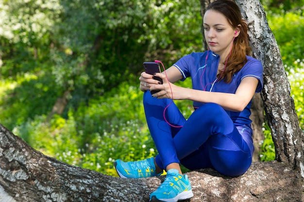 Sportswoman is listening to music  with pink headphones while havining a rest, sitting on the crouched tree in the forest alone